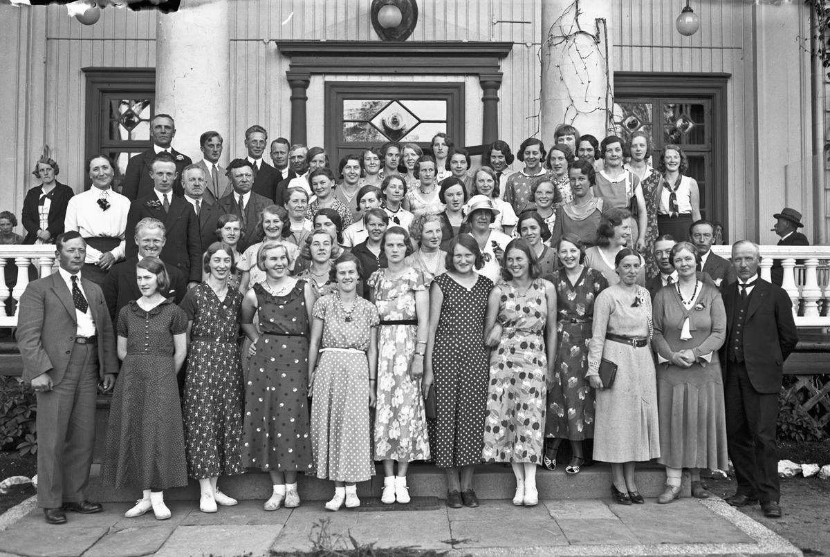 Gruppe kvinner og menn. Bestyrer på Akershus Fylkes Husmorskole Helene Hval ute til venstre.