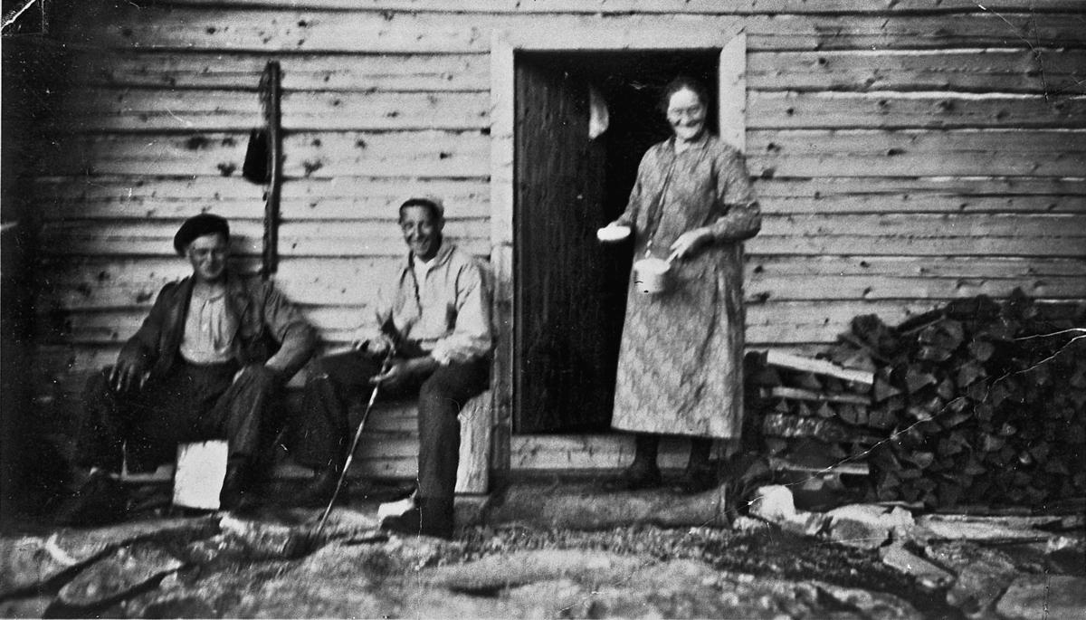 Kvinne og 2 menn utenfor et tømmerhus.
