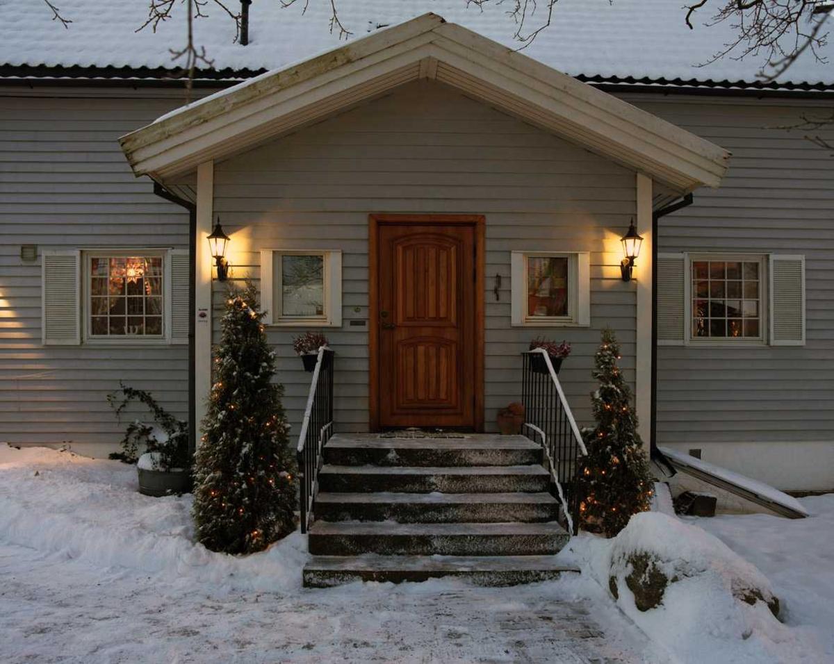 Julebelysning  Hvit julebelysning i lenke på to smågraner ved inngangsparti ved enebolig
