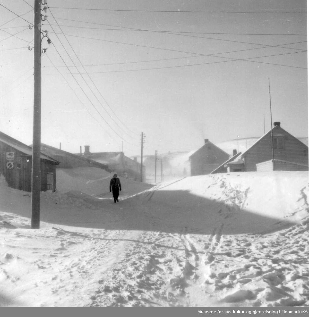 Snøforholdene i J.M.Withsgt. Fotoet er tatt fra Storgt og oppover. Til venstre Svein Johansens brakke-butikk. Det store huset øverst til høyre er Sandmohuset. 1952