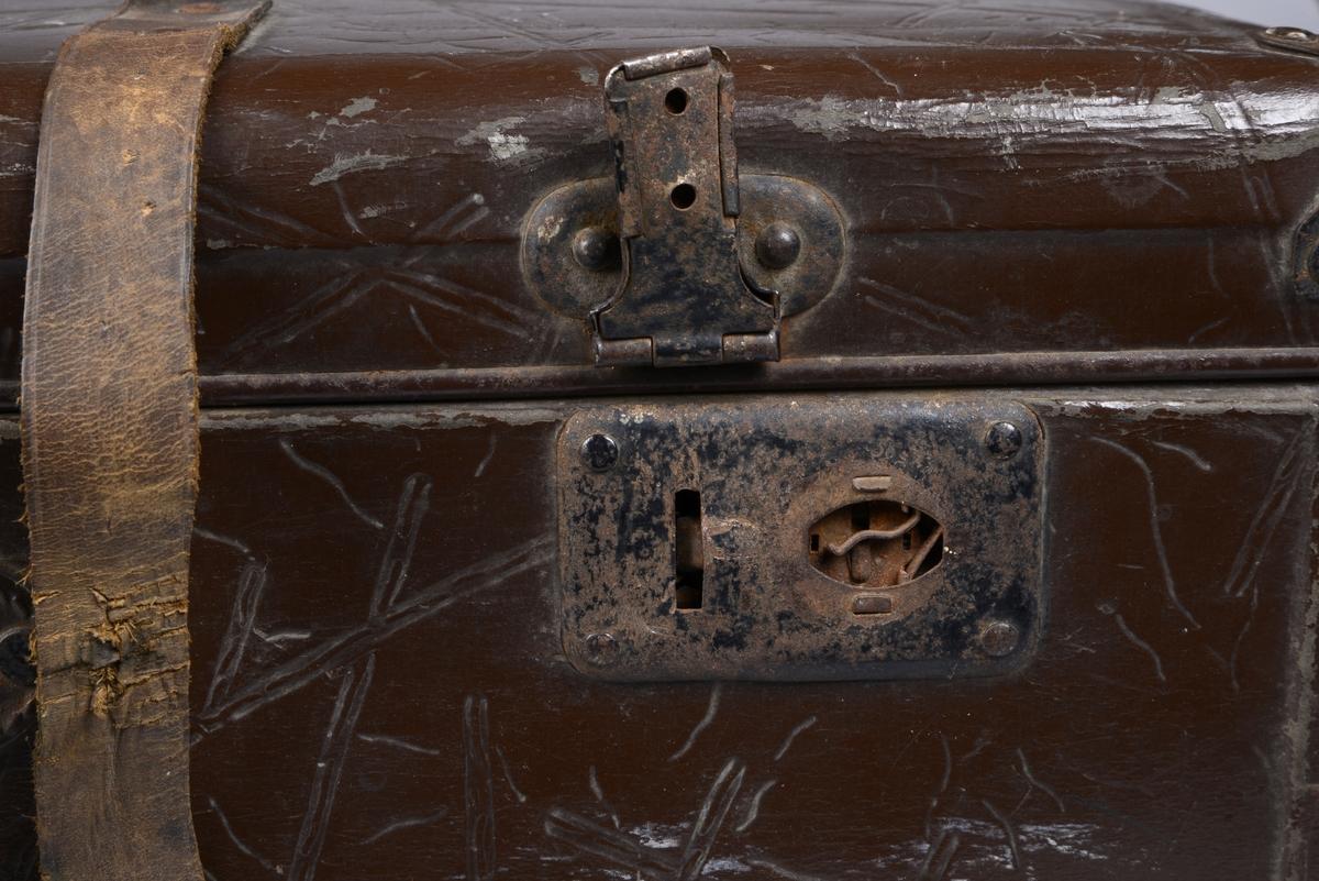 Koffert med kjerne av tre dekket med skinn.  Lokket har vært festet med to metallhengsler, disse har nå løsnet fra kofferten men henger fremdeles fast på lokket. To låser av metall, og et håndtak av metall. To skinnreimer er monterte på kofferten på låssiden. Kofferten er på innsiden trukket med papir med bølgende grafisk trykk.