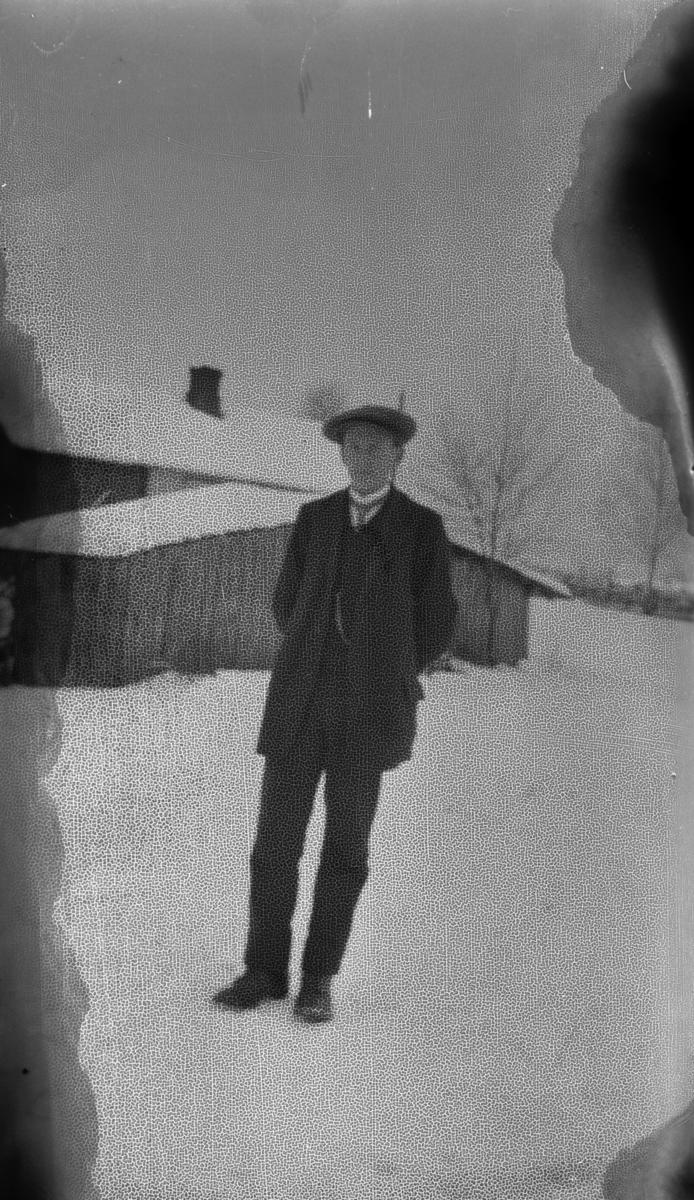 Ukjent gutt foran et hus, vinter.