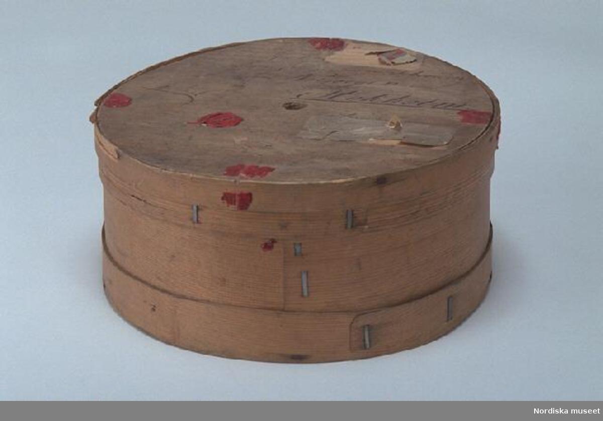 """Inventering Sesam 1997-1998: Diameter 29,5, H 15 (ca) cm Svepask, rund. Botten, lock och svep av furu, utan falsar. Extrasvep på såväl bottensvep som locksvep. Svepen fästade med spikar av järn. Hopfästning av svepen med krampor av tenn. Två trasiga pappersetiketter samt röda lackstämplar på lockets ovansida, inskrift med bläck, enligt huvudliggaren """" avsänd från Badenweiler till (drottningen) von Schweden und Norwegen, Stokholm"""". Har gått via Stralsund. Emballage för blommor. Innehåller mossa och rosenblad.  /Agnetha Blomberg 1997"""
