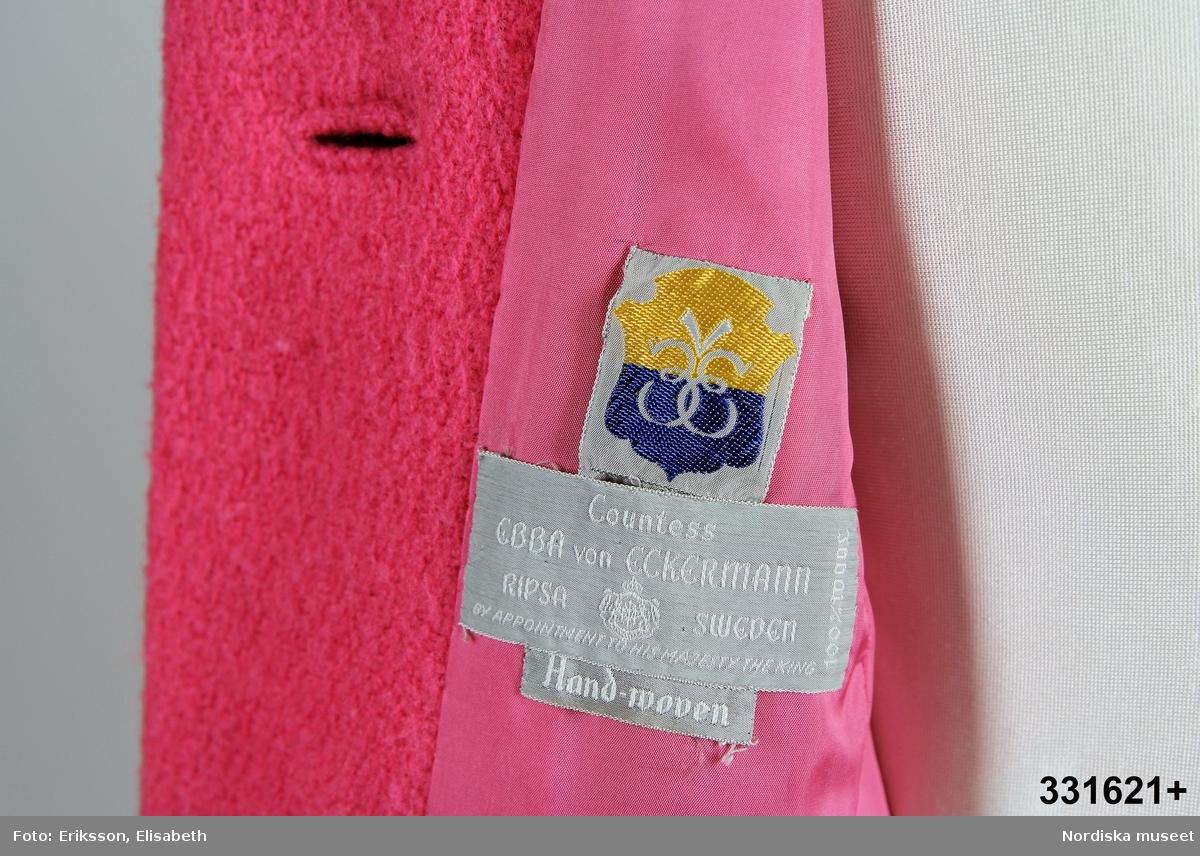 """Något utställd rosa kappa, prinsess-skärning fram, söm mittbak. Liggande krage, knäpps fram med fyra stora vitmålade träknappar, passpoalerade knapphål, trådhank och plastknapp under kragen. Fuskficklock med knapp och passpoalerat knapphål i höfthöjd. Ficka i sömmen, fram- sidstycke. Extra träknapp fastsydd i nederkant, en till lös i ficka. Ensömsärm med insnitt vid armbågen. Rosa foder, hank i nacke. Vidsydd tygetikett """"Countess EBBA von ECKERMANN   RIPSA SWEDEN    BY APPOINTMENT TO HIS MAJESTY THE KING 100% WOOL"""". Ytterligare en etikett """"Hand-woven"""" sitter i nerkant av första.  Löst skärp att knyta. /Magdalena Fick 2011-11-14"""
