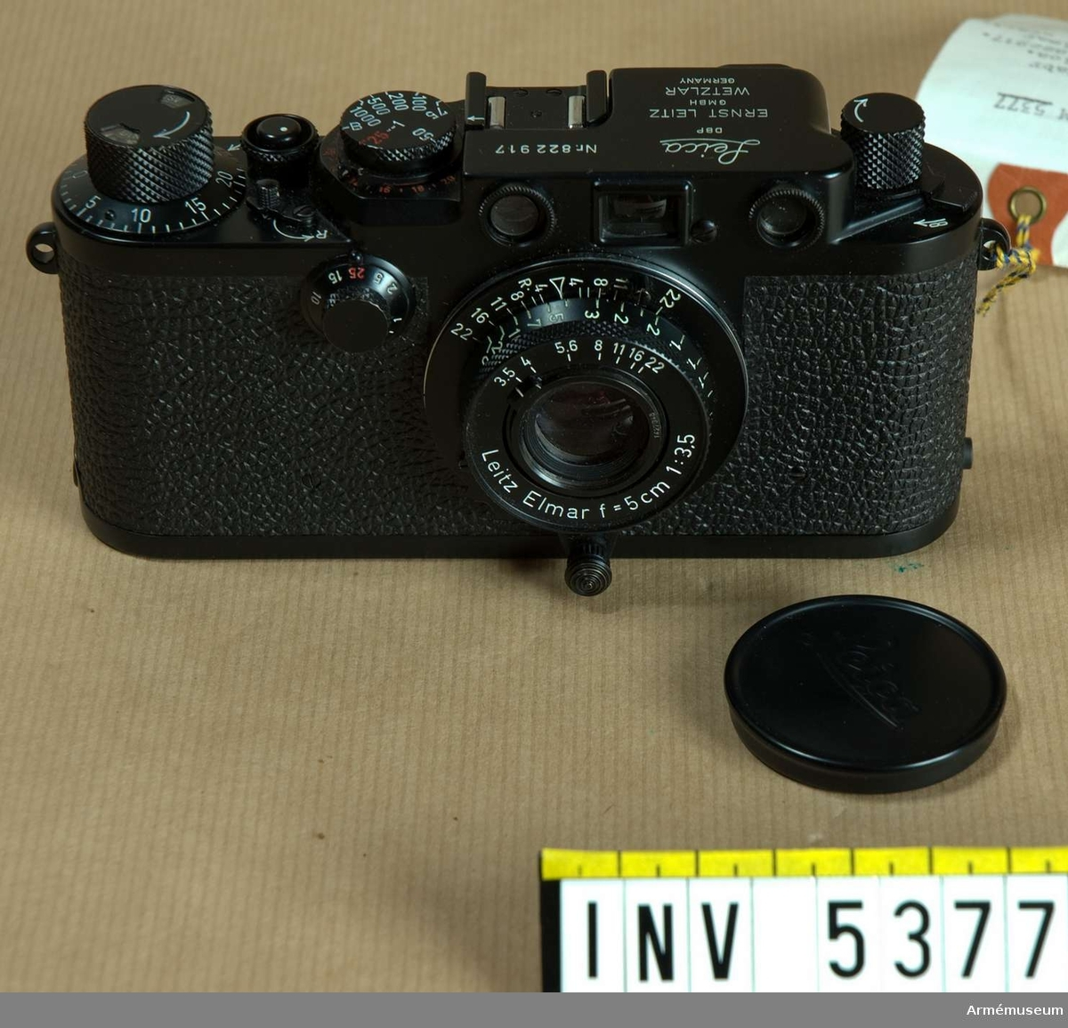 Samhörande nr är 5378, kameraväska.  Kamera 151, Leica, kamerakropp m objektiv.Tillv.nr: kamera 822917, objektiv 1427048. Kameran är svart med  vit och röd text liksom objektivet. Kameran har synkronisering  för blixt och röda kontakttal. Leicakassett finns i kameran.   Objektivet Elmar f=50 mm 1:3,5 är antireflexbehandlat; det är  inskjutbart och har svart lock. Dess mått är 40x47 mm.  Kameran och objektivet är inte märkta med emblemet tre kronor, men svarta objektiv av denna typ är ovanliga. Kameran och  objektivet är i mycket gott skick eller oanvända. Slutaren  fungerar tveksamt.  Enligt Ulf-Göran Hjort-Andersén, Armémuseum, är kameran troligen  av modell III g.Tillhör fotomaterielsats 7, låda 3.  1992-02-27 packad i låda / Erik Walberg.