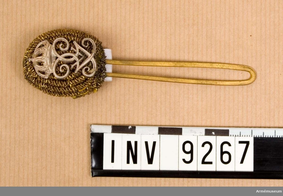 Av guldtråd för officer med regerande konungs namnchiffer i silver. I detta fall Gustav V:s namnchiffer G V. På baksidan hål för pompongnålen som fästes i vapenplåten.