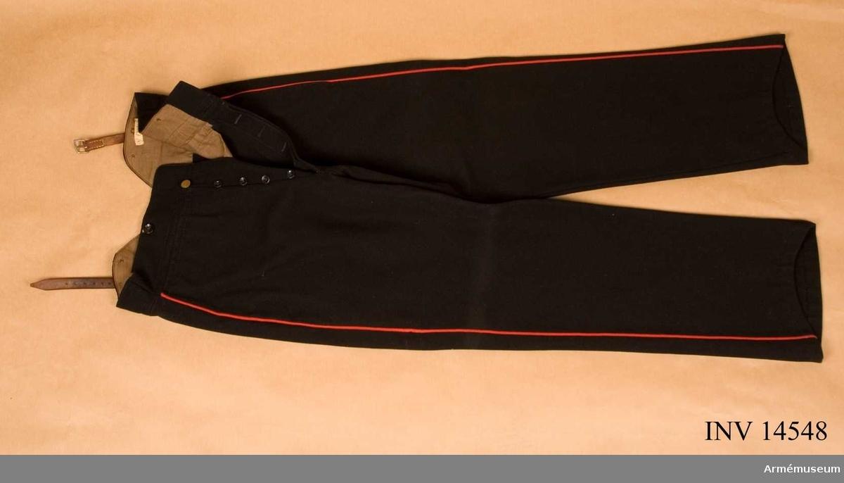 """Grupp C I. Långbyxor, meniga, 9. infanterireg. Av mörkblått kläde. Röda passpoaler på sidorna. Två sidofickor, en på vardera sidan, som stänges inuti med svarta knappar.  Foder av grått bomullstyg. På framsidan ett sprund med 4 svarta knappar och en stor mäs- singsknapp. För hängslen finns 4 svarta knappar. På baksidan finns spänntamp av remmar med järnspännen.   Lös ettikett me text """"Klädesbyxor -  Belgisk modell - bekommen 1883""""."""