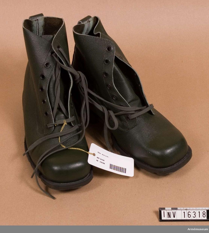 Av grönt läder, med svart gummisula och grön kängsnörning.