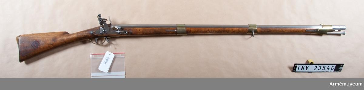 """Grupp E II.  Loppets rel längd 55 kaliber. Utgångshastighet 382 m/sek = 1285 fot. Kulvikt 30,6 gr. Kulans d:17,5 mm. Krutladdningens vikt: 9,98 gr. Kallat """"1815 års andra modell"""". Med undantag av fängpannan är detta gevär fullkomligt likt AM 1932:4208.  PIPAN är rund, utom längs bak, där den på var sida har en kort, platt för att den skulle kunna sitta stadigt i skruvstycket då svansskruven uttogs. Längst bak är diametern i vertikalled 34 mm men mätt över plattarna 32,5 mm. Vid pipmynningen är d:21,7 mm. Det 22 mm långa mässingskornet sitter 97 mm bakom pipmynningen. Den 14 mm långa bajonettklacken sitter på pipans undersida 33 mm bakom mynningen och 64 mm från mynningen finns en i näsbandet och framstocken infälld stadig stötklack. Den med bred, infilad siktskåra försedda avrundade siktbalken sitter längst fram på svansskruvstjärtens översida. Baktill på pipans översida finns en kronstämpel och en kron- stämpel en stämpel med krönt NT (Norrtälje). På V platten ett otydligt N och på undersidan 2 samt P. Korsskruven går nedifrån.   LÅSET fasthålles av två skruvar, har studel och varhake samt platt, i jämnhöjd med stockens yta infällt bleck. Hanens hals och platt har fyrkantigt tvärsnitt och är ganska tunna. Baktill, nedanför underläppen, fortsättes så att säga den bakåtsvängda  hanhalsen av en nedböjd flik, """"hanstjärt"""". Läppskruvens undre del går ut genom underläppen mellan hanhalsen och hanstjärten. Det korta, päronformiga läppskruvshuvudet har såväl skåra som hål. Hanskruven har stort, avrundat huvud. Pannskruven går inifrån.   FÄNGPANNAN är av brons och har arm. Dess överkant går i uppåt böjd båge framifrån bakåt. Eldstålsbladets övre del är tvärt böjt framåt och bildar """"tumstöd"""". Deckeln har på undersidan en utanför fängpannans bak-, ytter- och framkant liggande """"vattenkant"""". Eldstålsfjädern tryckgång är bågformigt upphöjd och fjäderns bukt är krökt nära nog i en halvcirkel. Denna fjäder är fasonerad. Alla skruvar samt överläppen är blånade. Låsskruvarna har stor"""