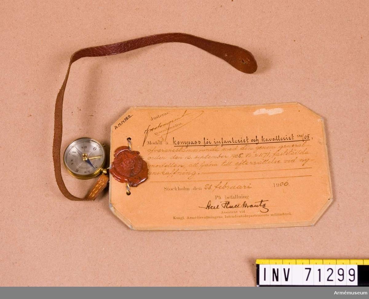 """Grupp C:II.  Vidhängande modellapp: """"Justeras: F. Holmquist Generalintendent. Modell å kompass för infanteriet och kavalleriet m/05, öfverensstämmande med den genom generalorder den 16 september 1905, n:r 1171, fastställda modellen, att tjäna till efterrättelse vid nyanskaffning. Stockholm den 28. februari 1906. På befallning Axel Hultkrantz Assistent vid Kungl. Arméförvaltningens Intendentsdepartements militärbyrå.""""."""
