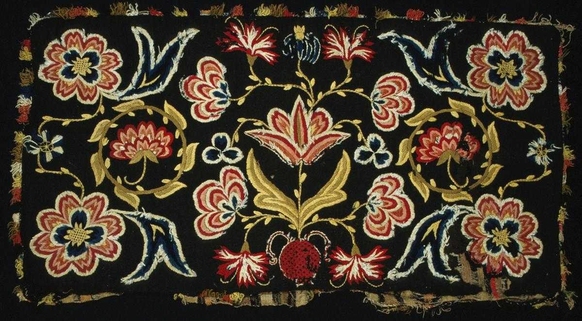 Dyna i skånskt yllebroderi i 2-trådigt z-tvinnat ullgarn i fyra nyanser rosa och rött, tre gröna nyanser och två blå nyanser, samt naturvitt och gult. Mörkbrunt tuskaftat bottentyg i entrådigt ullgarn, en 17 cm bred remsa är iskarvad i ena kanten. Mönsterformer av blommor och blad. I mitten en tulpan, nejlikor i en kruka sydd i rutsöm. Tolvbladsrosor i hörnen. En bladkrans med ros i på var sida om mittmotivet. Stygn: Schattersöm (oliksidig plattsöm), stjälkstygn, knutar, rutsöm, flätbottensöm. Baksida: Vävd i tuskaft i olika bruna nyanser i 1,5-2 cm breda ränder, samt en enda smal röd rand. Inslag i 1- trådigt lingarn (6,5 tr/cm), samt 1-trådig och 2-trådigt ullgarn. Varp i 2-trådigt lingarn (s-tvinnat). Dynan är öppen på ena långsidan, rest av knytband (?) i siden. Vävd frans i olika färger runtom, som är mycket sliten.