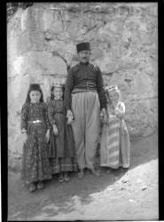 'Grupp med 1 man och 3 barn, flickor stående framför vägg. K
