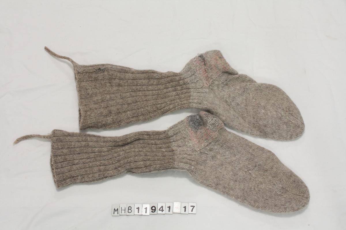 Grå strikkede sokker. Ankel/leggpdelen har vertikale striper laget med to rette og to vrange masker strikkes annenhver. En hempesnor på hver sokk i avslutningskanten.