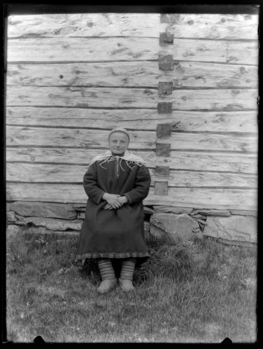 Samekvinne i kofte fotografert utenfor et tømmerhus