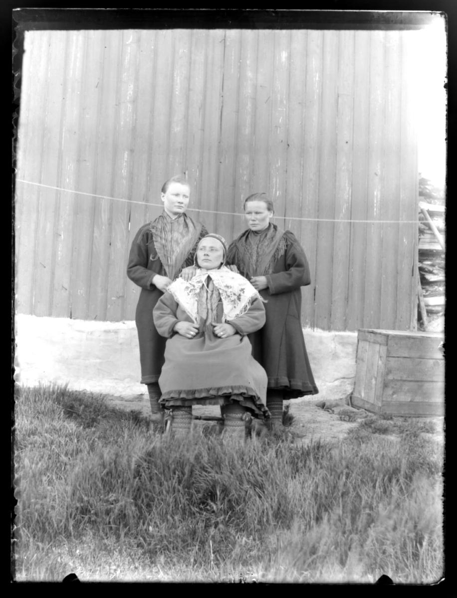 Tre ukjente samiske kvinner fotografert foran en husvegg