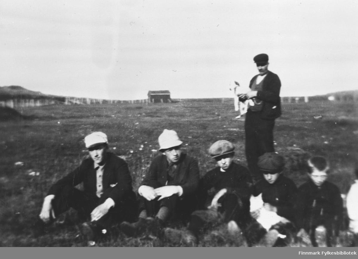 Fem brødre er fotografert sittende på bakken med sommerfjøset i bakgrunnen.  Fra v. eldstemann Erling, Hendry, Odd, Harald og Trygg. Faren Sevalders står bak og holder hunden Flink i armene.