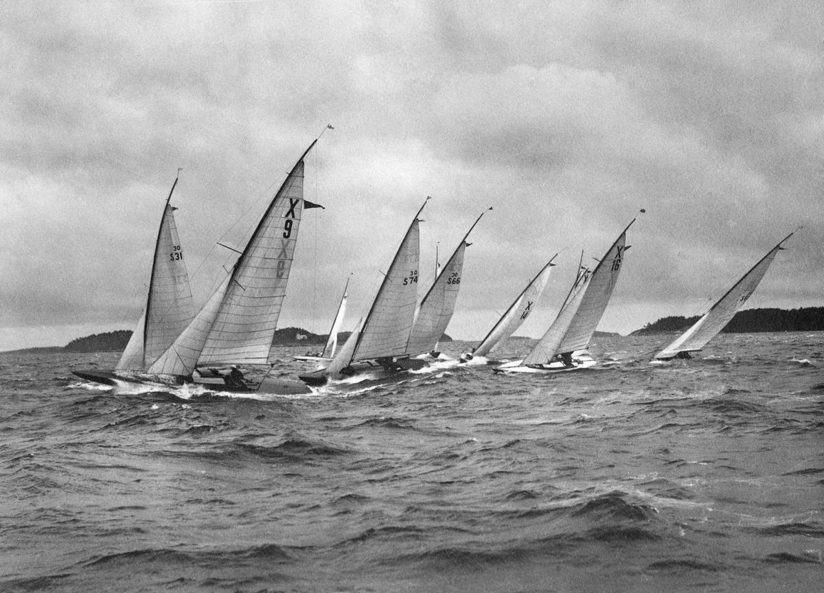 Fartyg: SMUT                            Rederi: Raben, Johan Byggår: 1925 Övrigt: Från Sandhamnsregattan 1926. Bakom X9 SMUT skymtar 30-S31 SSS 1926 (senare LINDAGULL II; b. 1926, konstr. Karl Einar Sjögren), därefter följer 30-S74 AHA (b. 1926, konstr. Tore Holm), 30-S66 NORNAN IV (skymd; b. 1924, konstr. Karl Einar Sjögren), X14 och X16 (tyska jakter, identiteterna ovissa) samt längst t h 30-S61 COBRA (b. 1925, konstr. Karl Einar Sjögren). Fotografiet återgivet i KSSS årsbok 1927 s 183; där framkommer att den aktuella kopian är beskuren och att en båt längst t v på negativet därvid fallit bort.