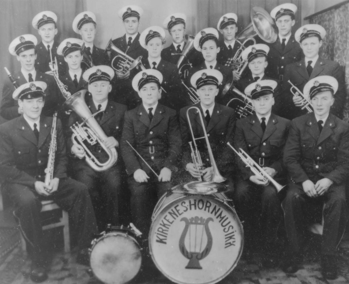 Kirkenes hornmusikk. Ingen årstall. Det er bare menn med, de er kledt i uniformer og oppstillt med instrumentene sine. Dirigenten sitter fremst, i midten.