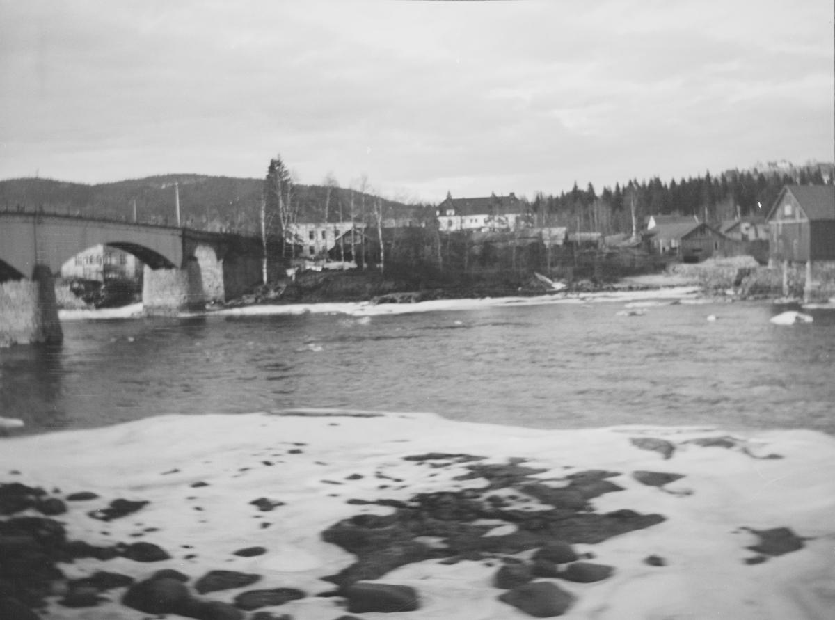 I front sees en snøkledt strand mot en elvestrøm med steiner. En bro går over elva. På den andre siden sees landlig bebyggelse. Hvite bjørkestammer lyser i landskapet.