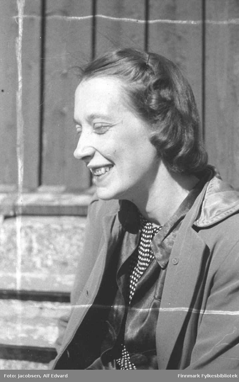 Aase Randi Jacbosen fotografert i solskinnet våren/sommeren 1945. Hun har en ganske lys kåpe/jakke på seg. Under har hun en mørk bluse eller vest. En mørk t-sjorte med hvite prikker kan ses fra halsen til midjen. En hårnål står i håret hennes  på venstre side av hodet. Hun sitter inntil et hus på Lødingen som har stående panel. Litt av kjellermuren ses nede til venstre på bildet.