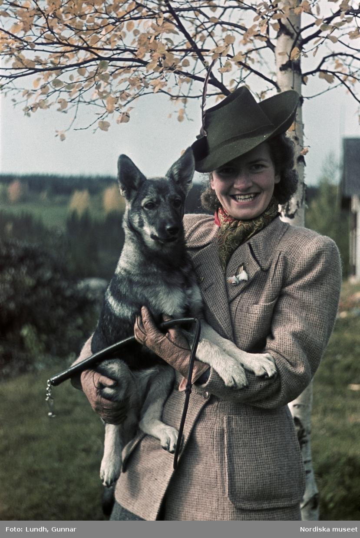 Kvinna klädd i tweed med en hund  i famnen och en läderpiska i sin hand.