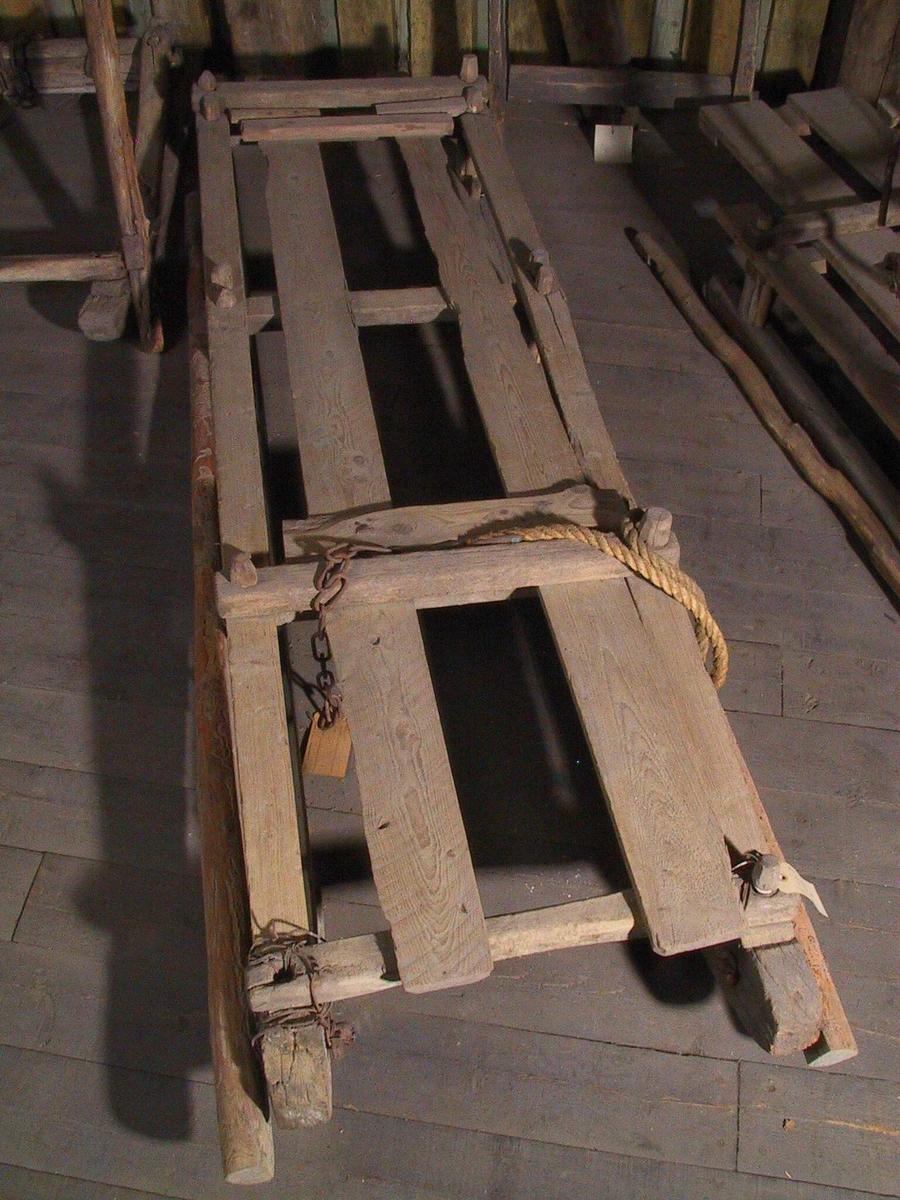 Arbeidsslede. Eik. Langsgående planker oppå, et bord er ikke høvlet, bare avbarket. Umalt.