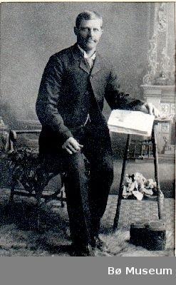 Olav G. Nyhus (tidl. Plassen eller Folkestad) frå  Bø sitjande i fotoatelier i Amerika