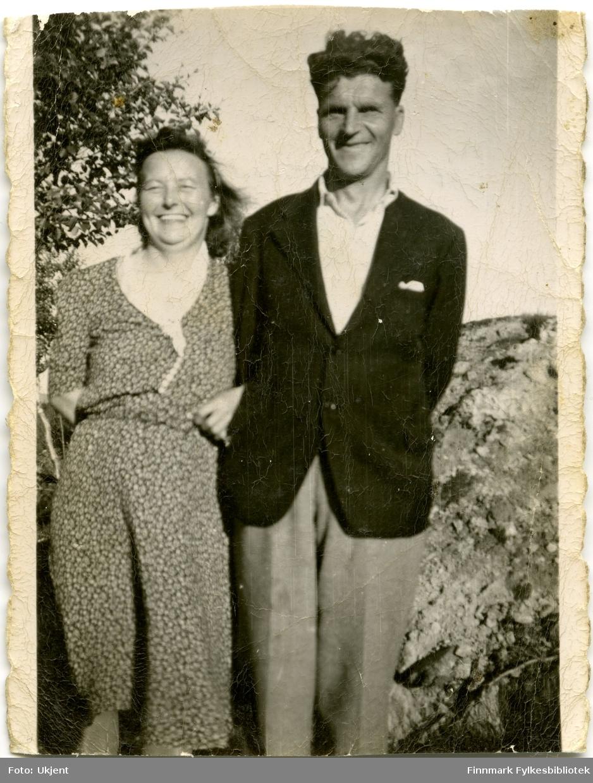 Et portrett av ekteparet Johanna og Petter Aule tatt i Kirkenes. Johanna er kledd i kjole og Petter har på seg jakke, skjorte og bukse. I bakgrunnen kan man se stein og et tre.