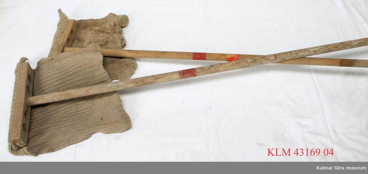"""KLM 43169:4 Brandsvabb, 2 st, trä, textil. Smalt cylindriskt skaft av trä med i ena änden en tvärställd rektangulär träbit med stora borrade hål. Vid träbiten är fäst en trasa av textil. Skaftet är märkt med en röd målad rand. På den ena sitter en röd etikett (skadad) med delvis läsbar text """"...inspektionen""""."""