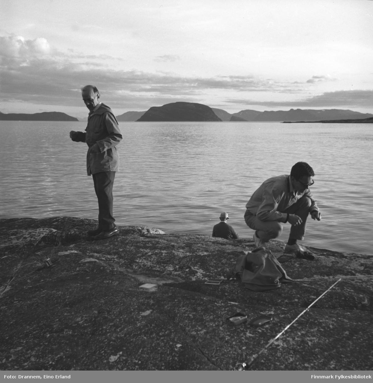 Tre ukjente menn på fisketur i fjæra ved Hammerfest. Fuglenesodden ses til høyre på bildet og øya Håja midt på bildet.