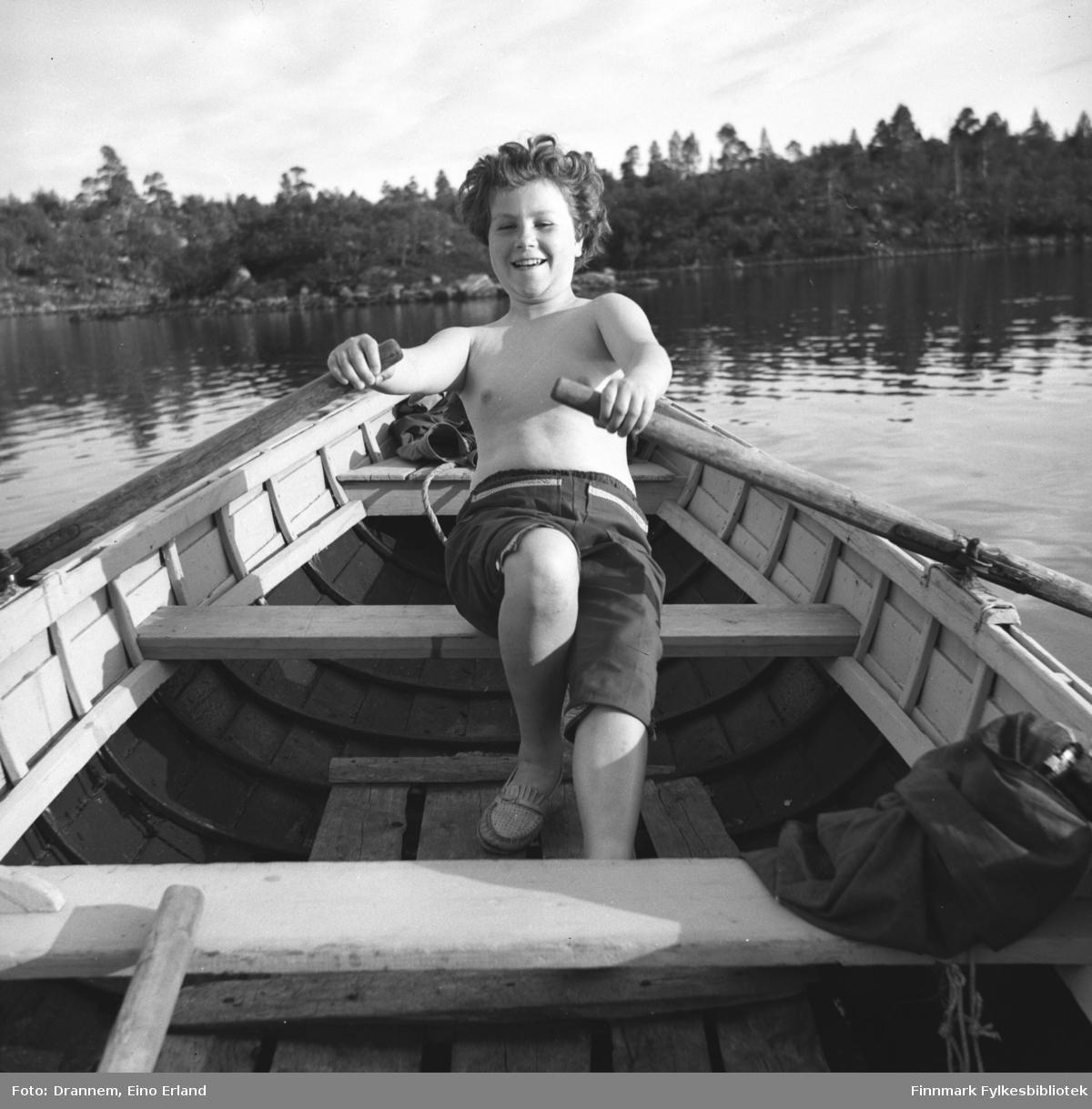 Turid Karikoski ror på en blikkstille innsjø.