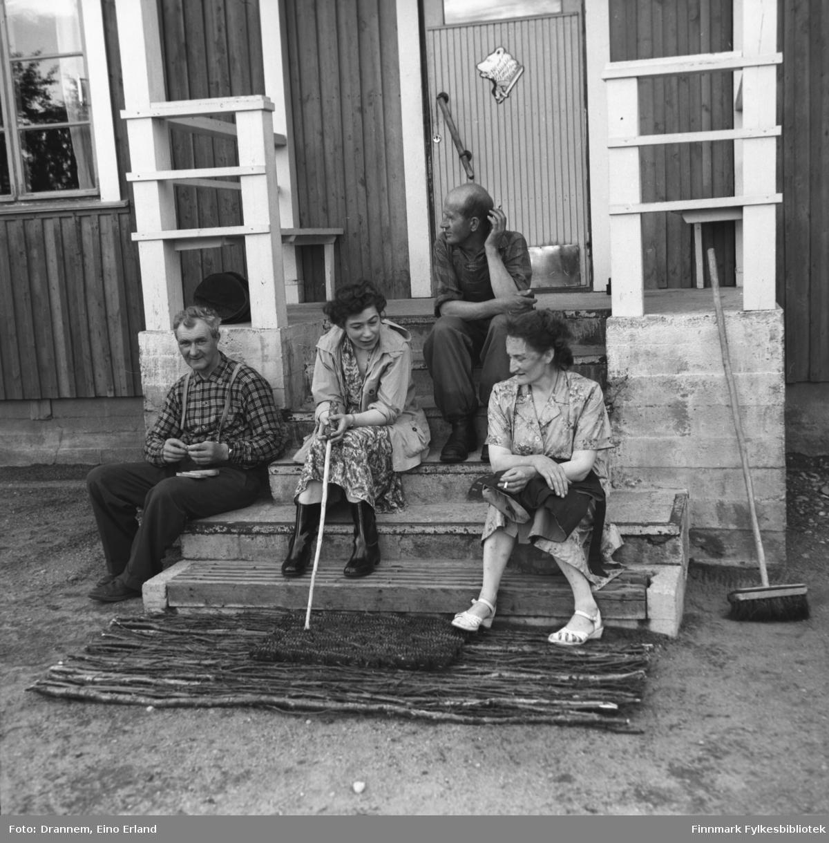 Fire personer sitter på trappa til grensevaktstasjonen på finsk side i Neiden. De er, fra venstre: Søren Gabrielsen, Jenny Drannem, Uuno Lappalainen, ukjent.