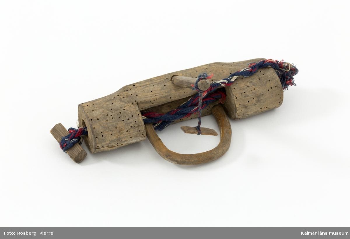 KLM 45736. Råttfälla. Av trä och bomullsgarn. Består av en avlång träbit med ett hål rakt igenom. I hålet sitter en flätad snodd av tunt bomullsgarn i vitt, rött och blått. Mitt på en bygel av ene med en pinne ovanför i vilken det hänger en träbit i ett flätat snöre. Någon form av tyngd, träkloss, saknas.
