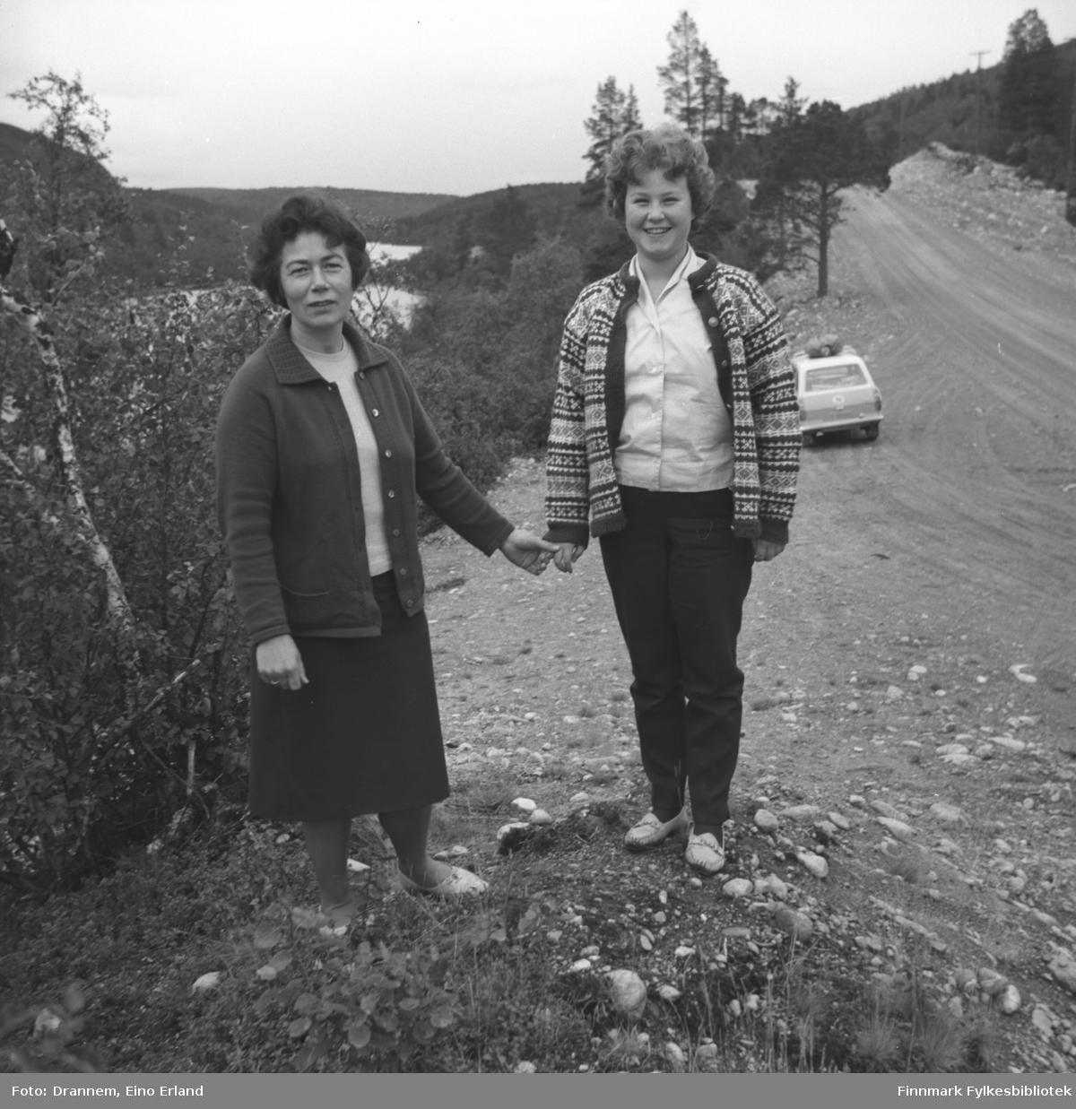 Jenny Drannem og Turid Karikoski står ved en grusvei. Bildet er muligens tatt i Neiden i Sør-Varanger.