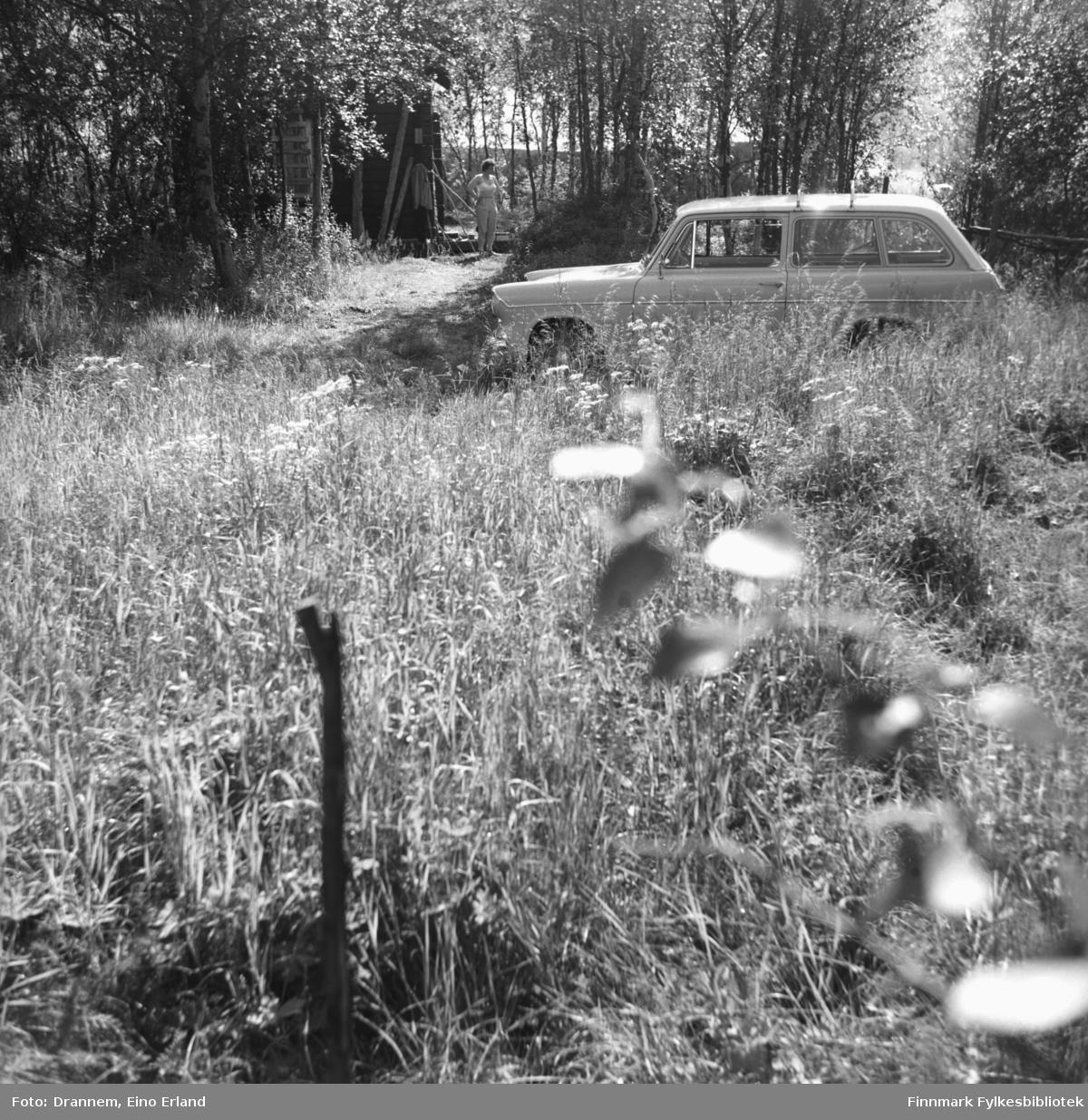 Familen Drannems bil parkert på en gårdsvei i Neiden. Jenny Drannem står utenfor hytta.
