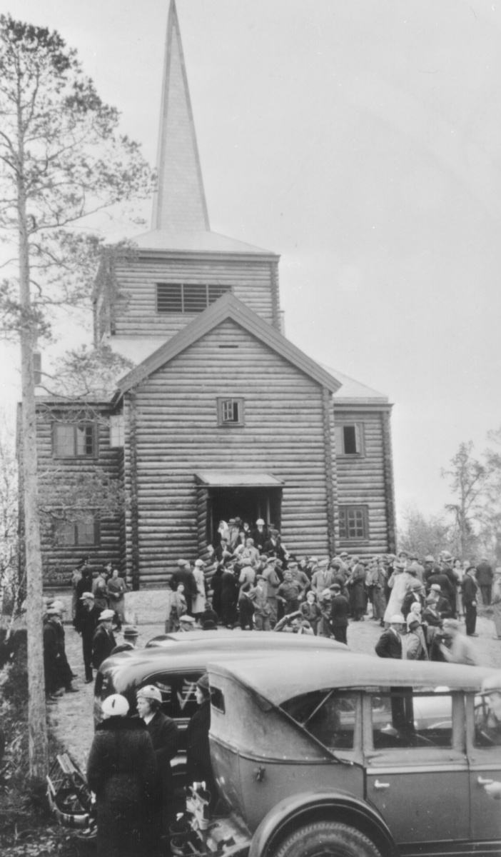 Gudstjeneste i Svanvik kapell er over. Folk er på vei ut av kapellet.Tre biler fra 1930-åra står i forgrunnen. Det er mye folk på bildet. Kapellet ble bygd i rundtømmer og ble innvidd i 1934.