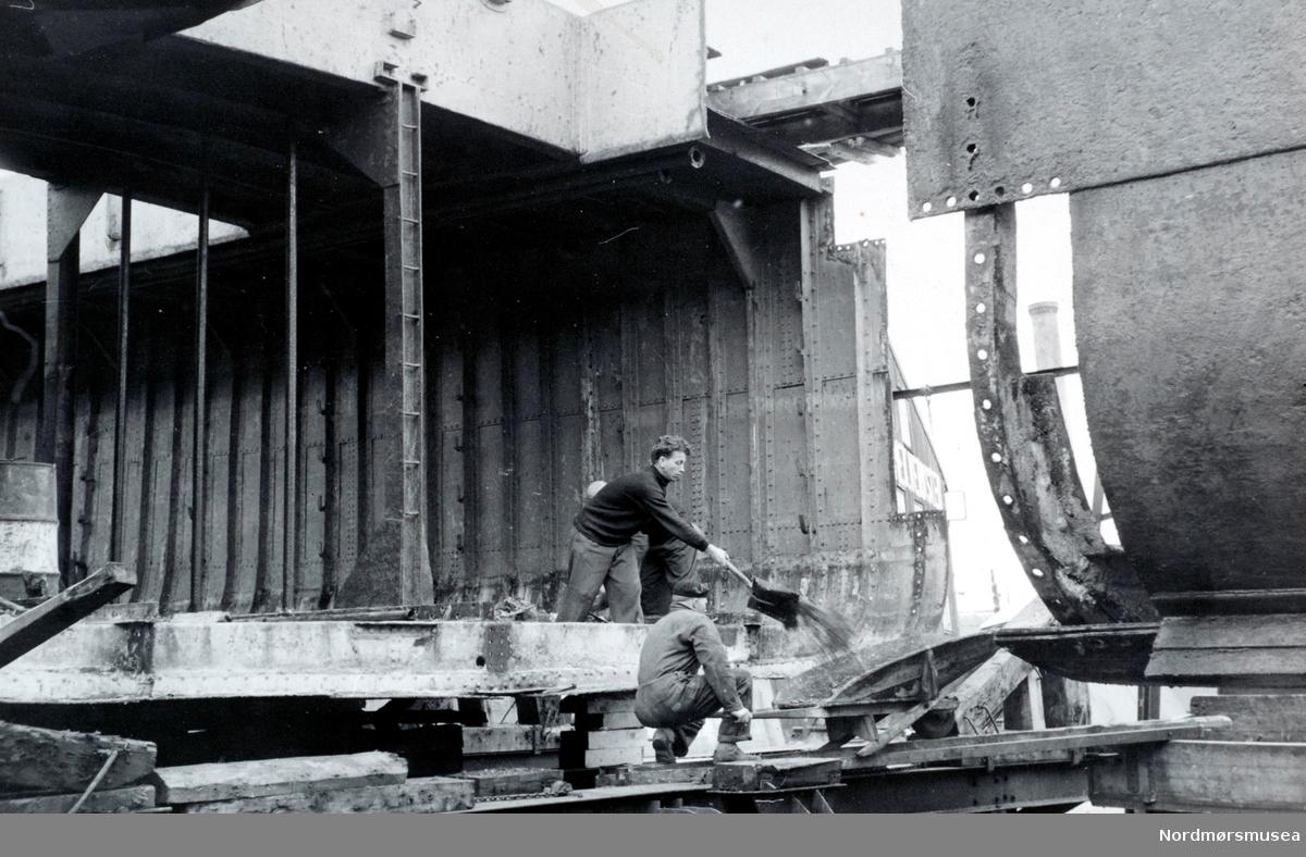 """Bildet er fra forlengelsen av M/S """"Vestkyst I"""" på den nye patentslippvogna ved Storviks Mek. Verksted på Dahle ved Kristiansund, klinkbygd i stål 1918 og var den største slippen mellom Bergen og Trondheim. På bildet er båten trukket fra hverandre på patentslippen. Personene på bildet er ukjente. M/S""""Vestkyst 1"""" var bygget som singledekker som bnr. 27 ved Husø Verft & Mek. Verksted i Tønsberg og ble i mars 1924 levert til A/S Sørlandske Kystfart (L.S. Daae) i Oslo. Opprinnelig var skipet utrustet med en T3 Bergen MV på 39 nhk. Etter konkurs hos rederiet i 1927 ble skipet kjøpt av A/S Sørlandske Dampskibsselskap – fortsatt med L.S. Daae i direktørstolen.  I 1932 ble skipet overført til Arendal med Skips-A/S Kysten som ny eier. I oktober 1936 sank  """"Vestkyst 1"""" etter kollisjon og ble hevet av Brødrene Anda og Stavanger Skipsopphugging Co.  I 1937 var skipet reparert og igjen satt i fart.  29.septeber 1940 kolliderer """"Vestkyst 1"""" med slepebåten """"Storeknut"""" ved Skibeskjærene.  På ny synker """"Vestkyst 1"""" og den blir atter hevet og reparert. Under reise Oslo – Bergen i mars 1941 blir """"Vestkyst 1"""" skadet etter flyangrep ved Jæren og fire måneder senere blir skipet angrepet og skadet av britiske fly som førte til at skipet ble satt på land ved Skadberg utenfor Jæren. Her sank hun, men bro og bakk var likevel over vann. Brødrene Anda måtte igjen til pers for å heve fartøyet. I oktober 1942 er skipet på nytt reparert og satt i fart. Når Johan Aronsen kjøpte skipet i desember 1953 lå det i opplag i Arendal etter at det tidligere hadde gått i rutefart Oslo – Bergen. I april 1954 ble """"Vestkyst 1"""" ombygget til motorskip og fikk innsatt en M6 Vølund på 420 bhk. I 1959 ble skipet ble skipet forlenget til 161,7 fot ved Storviks Mek. Verksted i Kristiansund og ble i denne sammenhengen oppmålt til 419 bruttoregistertonn og 560 tdw. Johan Aronsen døde i 1966 og """"Vestkyst 1"""" ble i juni 1966 overført til Aronsens Rederi (Hans Aronsen) og solgt i 1967 til Arne Strøm P/R på Lyngseidet. De vi"""