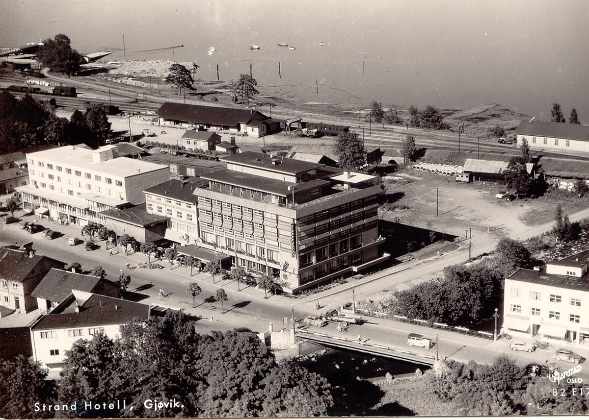 Flyfoto fra Gjøvik sentrum. Strand hotell i forgrunnen, jernbanestasjonen bak.