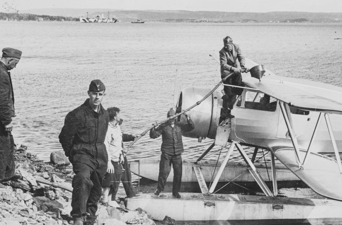 """Ved ambulanseflyets avgang til Nord-Norge. Flyver Hans Grøn Lund i midten (bak) med knickers. Tekst fra album: """"Tankene fylles."""""""