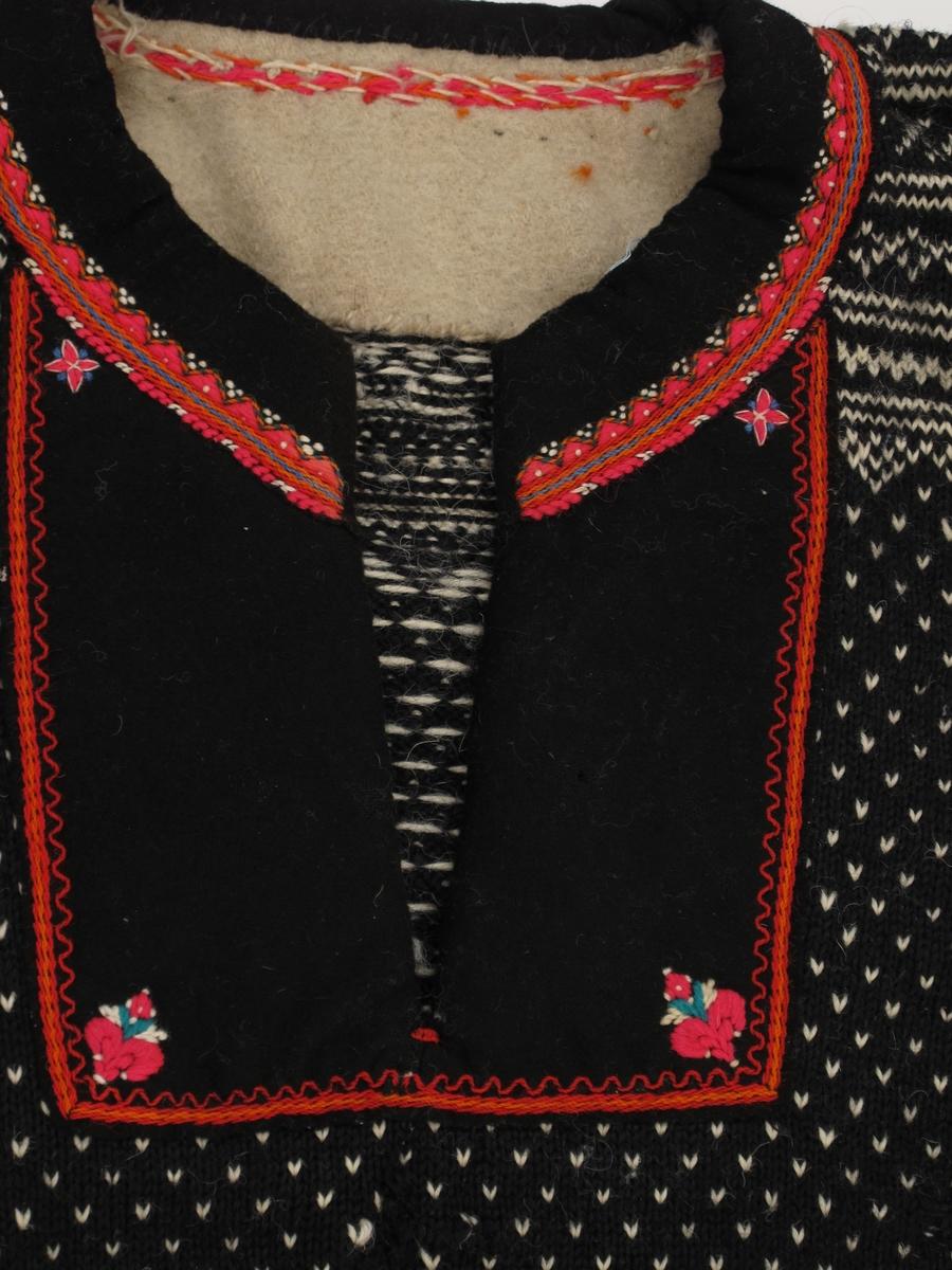 Strikket ull, sort med hvitt geometrisk mønster i border ved håndledd, skuldre og ved vrangborden, hvite lus ellers,  Påsydd kant av sort klede rundt halsåpningen med broderier i rød, blå og hvit ull.  Bred påsydd kledeskant med broderier med bryståpningen.  Påsydde mansjetter av sort klede, kantet med grønt klede, brodert i polykrom ull.  Hvit vrangbord i livet.  Notert på kopi av kort:  Kamgarn, maskinstrikket med enkelte innslag av håndstrikk.  Herebora ): bærestykke  skulderstykke av vadmel.  Klede m. løyesøm broderi.