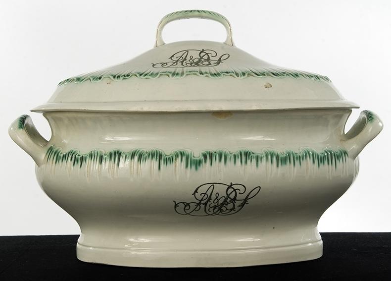 Stort, ovalt potetfat med lokk, del av servise fra tidlig 1800-tall. Hank på lokket og i hver ende av fatet. Grønn bølgekant og sort monogram, A & BS, i midten.