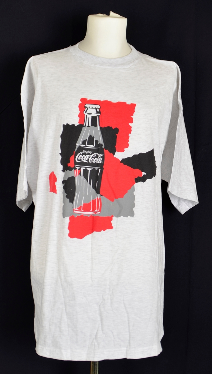T-skjorte i lys gråmelert bomull. Rund hals. Rett snitt. Trykk på begge sider. Trykt på: Ei flaske med Coca-Cola på raud og svart bakgrunn  framme, og tekst med program påskrive på ryggen.
