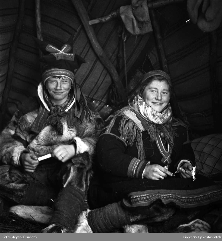 Mathis Johansen Sara og Inga Johansdatter Sara fotografert inne i lavvoen. Fotografert i Kautokeino i periden 1939-40. Begge er kledd i samiske drakter. Mathis bærer samisk lue, pesk og har skaller og skallebånd på beina. Inga har samisk kofte og lue med sjal i halsen. Et liknende bilde ble publisert i Nordmannsforbundets julehefte 1950 og Magasinet for alle nr. 13, 29.mars 1961.