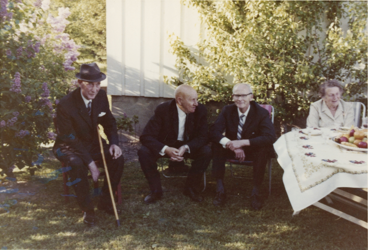 Tre eldre menn med dress og en dame sitter i hagen på Braate gård.