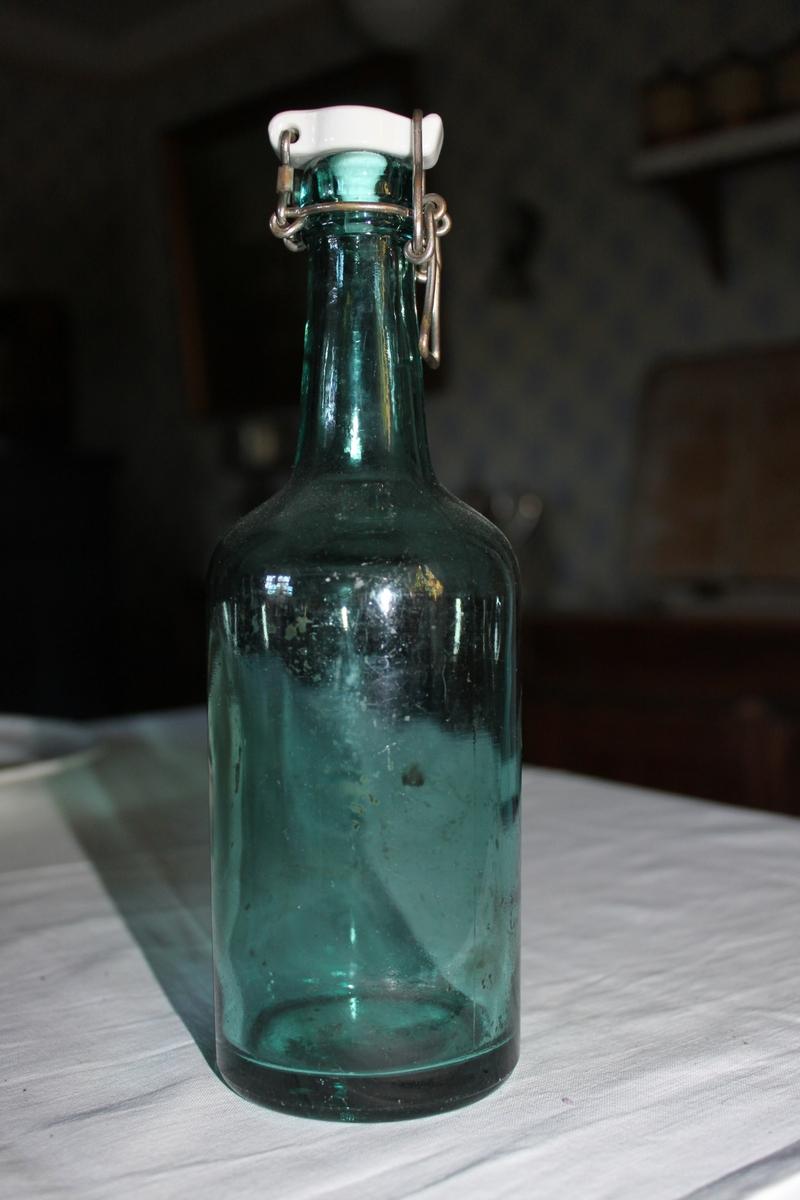 Glasflaska i genomskinligt grönt glas med vit porslinskork.