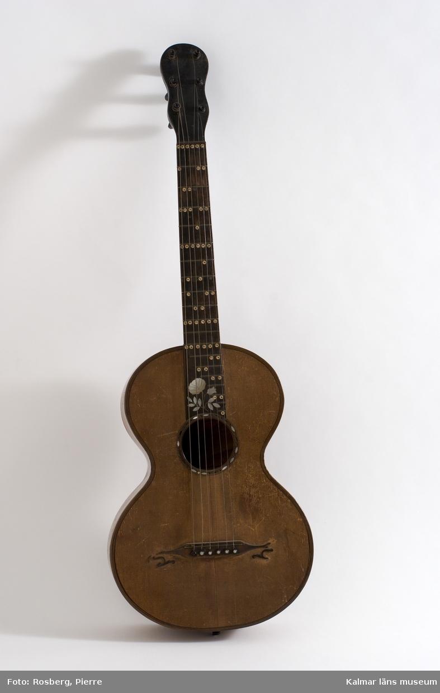 KLM 39707:1. Gitarr, av trä. Inlagd dekor av pärlemor i form av en ros med blad, på greppbrädets nedre del. Komplett med strängar.