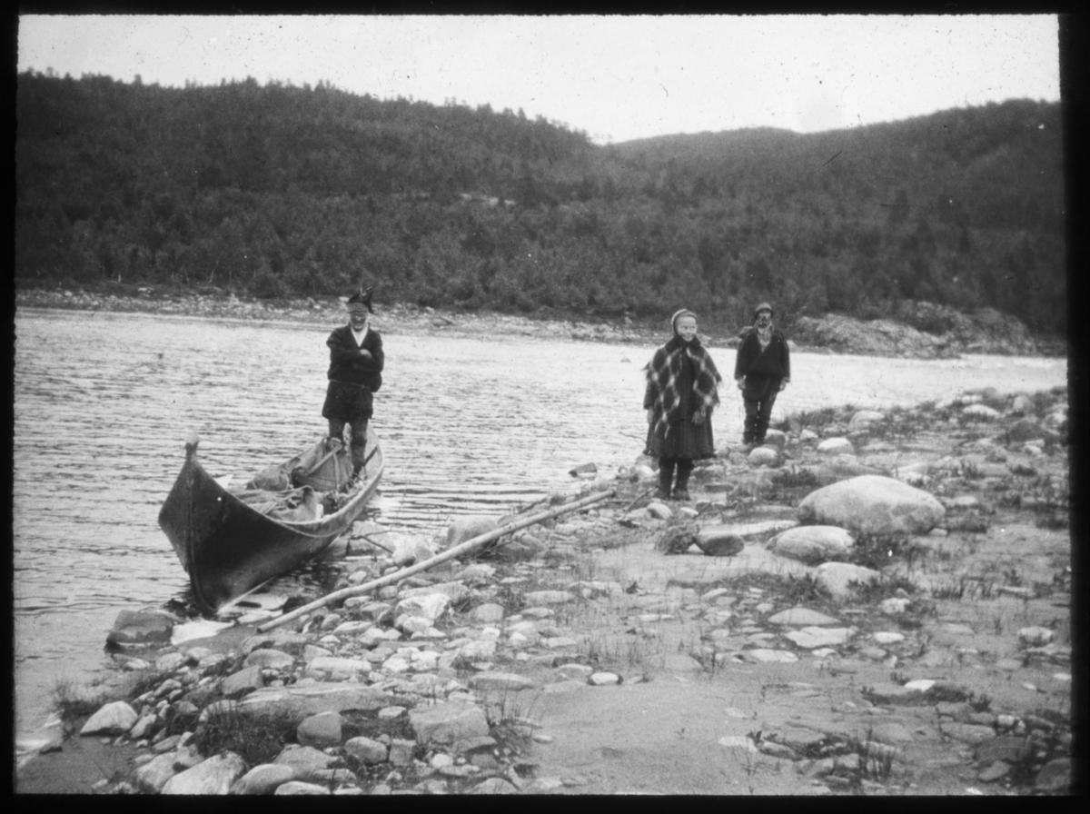 """""""Elvebåt på Karasjokka."""" står det på glasplaten. Elvebåten ligger på elvebredden, en same står oppreist i båten. Han er kledd i  samekofte og lue. På land står det en samisk kvinne, bak henne står det en mann kledd i samisk kofte med ryggsekk på ryggen og lue på hodet.  Det er mulig at disse to er passasjerer som skal reise eller har kommet i land fra elvebåten. Ombord i elvebåten ser man at det ligger en del sekker og utstyr. Det vokser skog på andre siden av elven."""