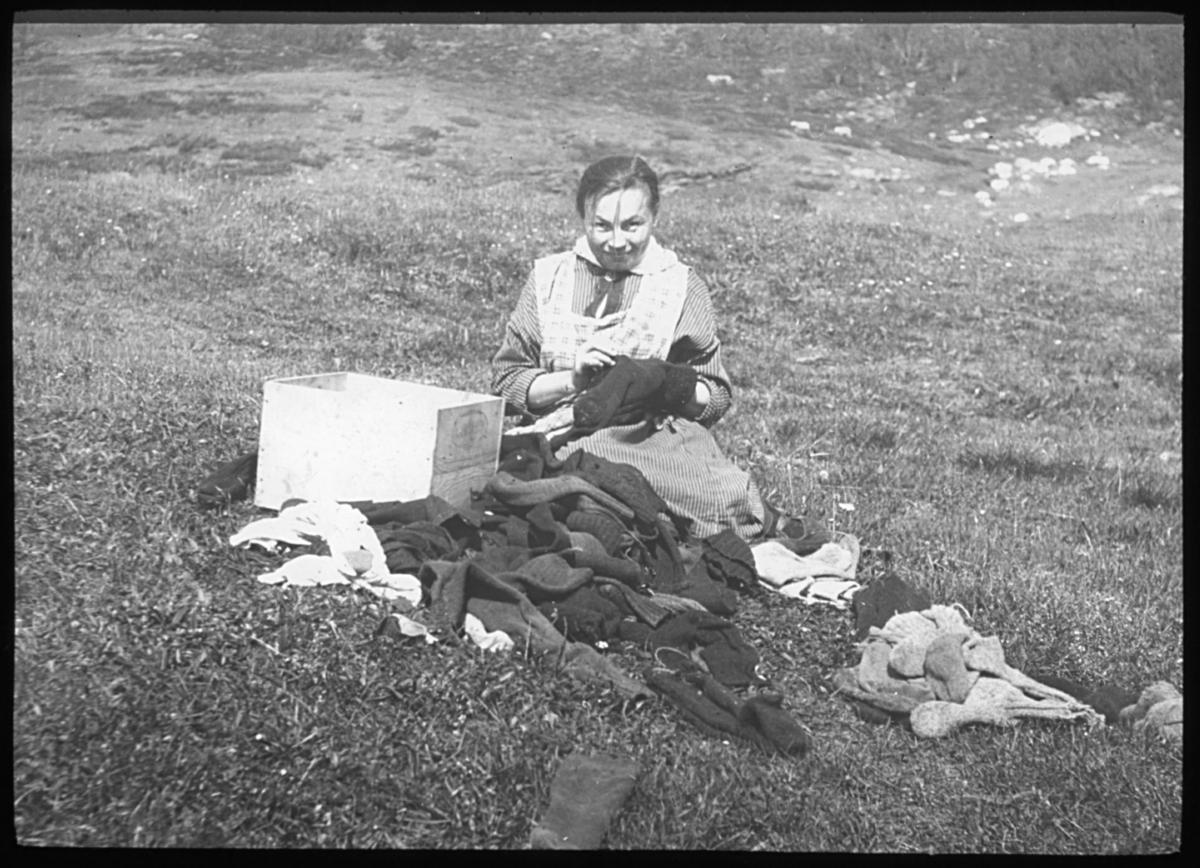 """""""Fra Rotsundelv. Strømpene skal stoppes."""" N.6. står det på glassplaten. Kvinne som stopper ullsokker i solen. Sokkene ligger på bakken og en trekasse står tom ved siden av. Vi kan anta at sokkene har vært samlet i kassen og hun sitter nå i solen og reparer hull i sokkene. Alf Schrøder reiste rundt og dokumenterte for Norsk Finnemisjons virksomhet og Rotsundelv lappiske barnehjem (tidligere Kvæangens) lappisek barnehjem ble drevet i  perioden 1886-1914. Sokkene som kvinnen stopper er derfor muligens barnehjemsbarnas sokker."""