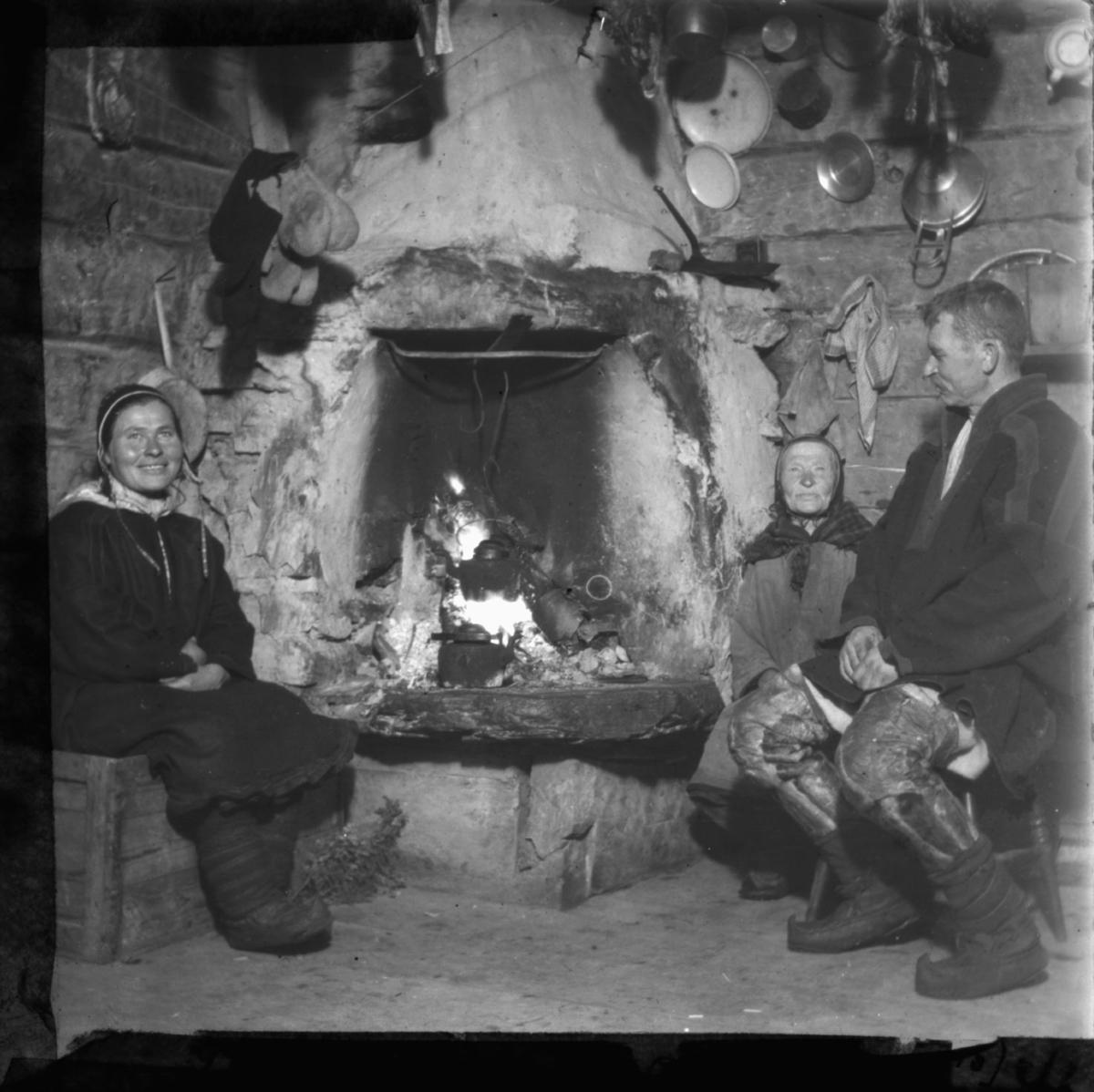 """""""Idyll ved gruen. G.15. 41"""" står det på glassplaten. Samisk famile sitter ved peis. Kaffekjellen henger over ilden. På veggene kan man se endel kjøkkenutstyr og på en snor henger det votter eller sokker til tørk. Alle har på seg samiske kofter, skaller på beina. Kvinnene har samisk lue. Mannen har også benklær sydd i skinn. Veggene er i tømmer. Peisen eller ildstedet i bakgrunnen."""