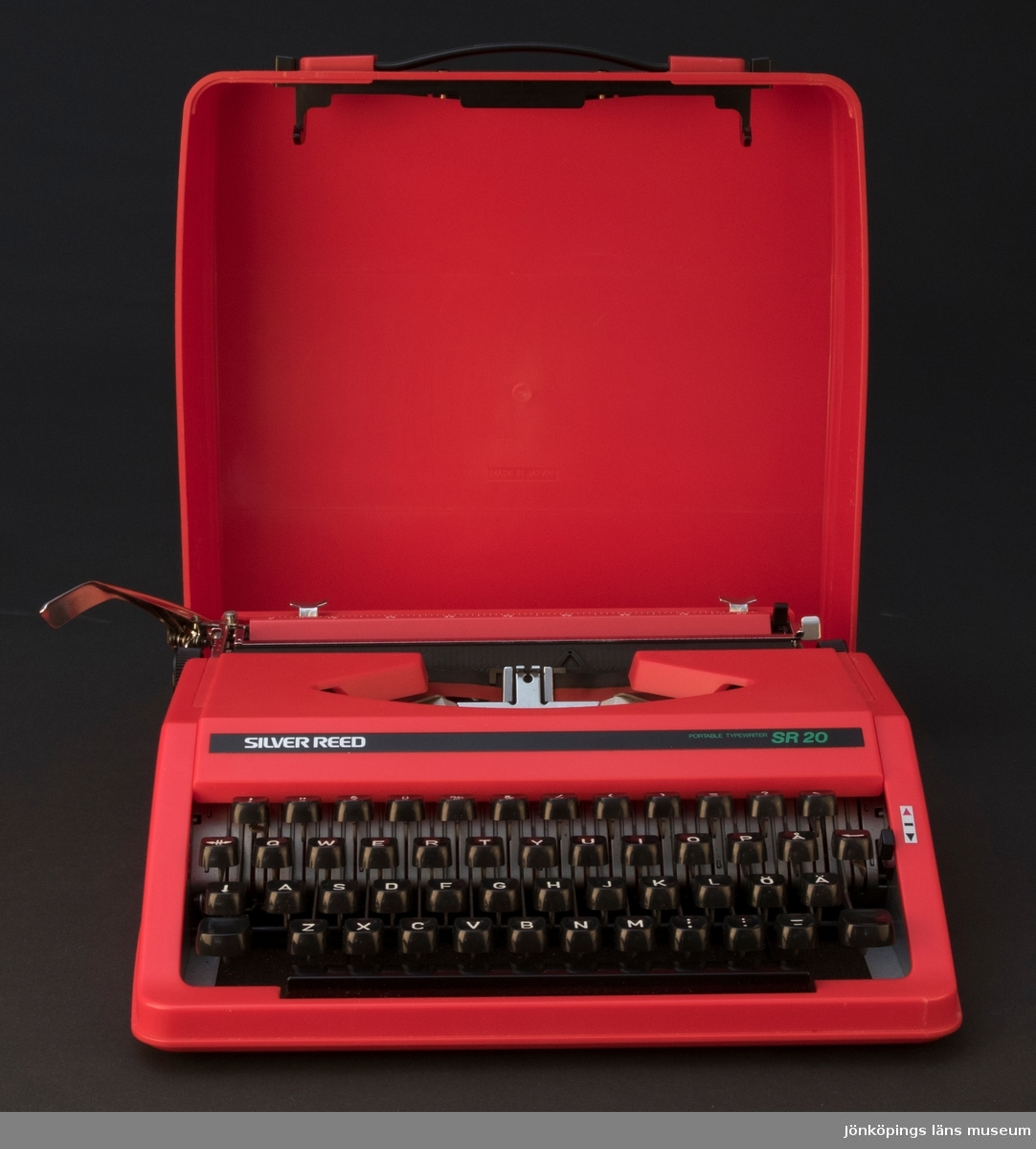 Skrivmaskin med lock (reseskrivmaskin) av röd hårdplast och metall. Modell Silver Reed SR 20. Färgband (svart och rött) är monterat i maskinen. Fyra svarta gummitassar sitter under skrivmaskinen. Locket har två svarta tryckknappar och handtag på framsidan, och två smala lister på baksidan/undersidan för att kunna ställa maskinen och väskan uppåt.  JM 43489:1, skrivmaskin JM 43489:2, lock